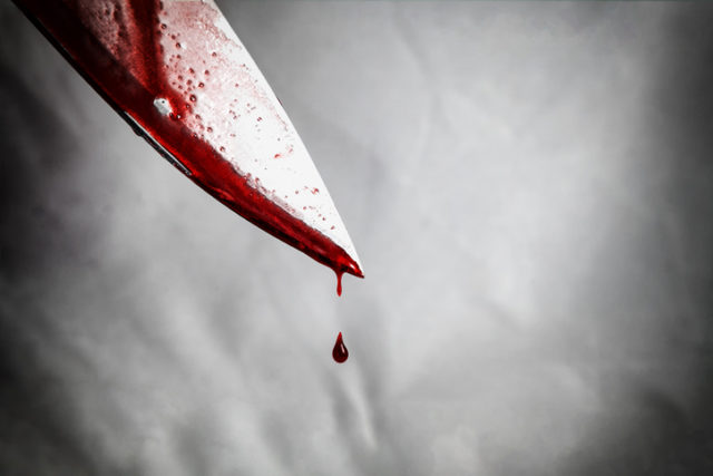 Close up of man holding knife smeared with blood and still dripping.