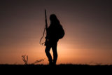 Woman Hunter Silhouetted in Sunset