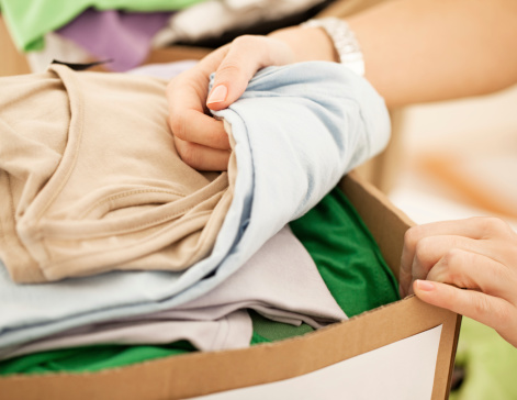 Female hands packing clothes into a donation box.