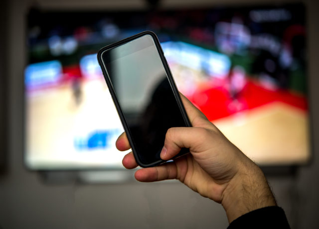 Man using mobile phone during a basketball match