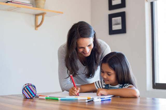 Mother helping daughter draw