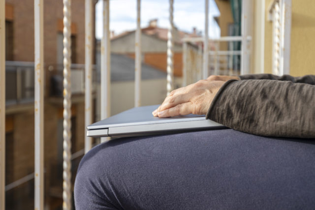 Woman with laptop on the balcony at home. Home office.