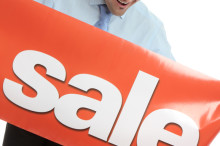 A happy salesman, businessman or other marketing person holding a vinyl sale banner.  White background.