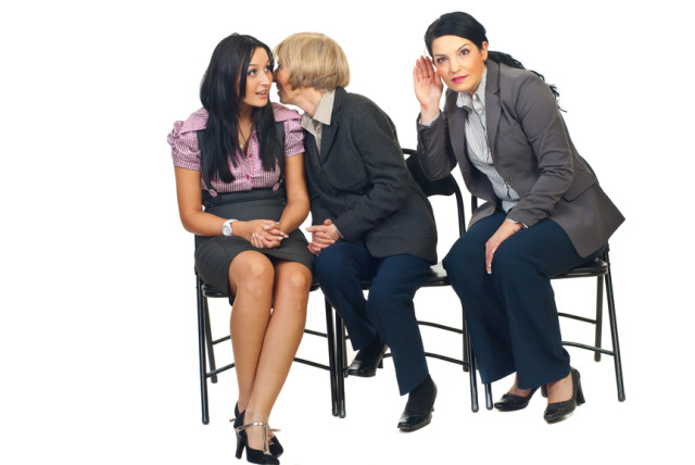 Senior business woman tell a secret to a colleague woman and other woman trying to hear what her colleagues saying and sitting all on chairs isolated on white background