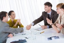 Business partners shaking hands after striking deal while their co-workers applauding