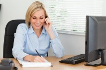 Cute blonde businesswoman on mobile writing something down in her office