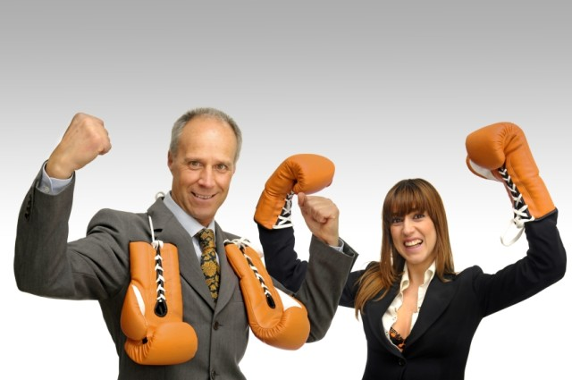 Business couple with boxing gloves isolated in white