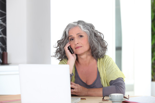 Senior woman on phone in front of laptop