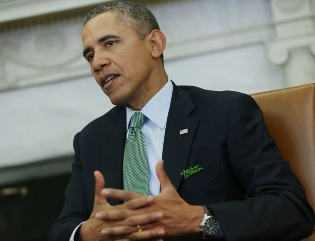 President Barack Obama, wearing a green tie and with shamrock in the breast pocket of his suit, makes a statement to reporters during his meeting with Irish Prime Minister Enda Kenny in the Oval Office of the White House in Washington, Friday, March 14, 2014. (AP Photo/Pablo Martinez Monsivais)