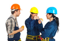 Team of three constructors workers in a break eating sandwiches and having conversation isolated on white background