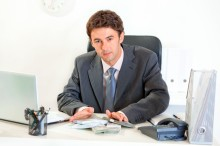 Modern business man  sitting at office desk and giving money packs