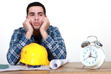 Construction worker with plans and an alarm clock