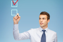 business and office concept - attractive buisnessman or teacher with marker drawing red checmark into checkbox