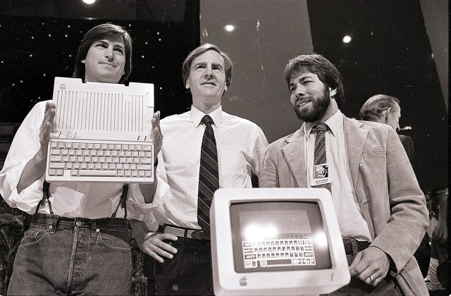 FILE - In this April 24, 1984, file photo, from left, Steve Jobs, chairman of Apple Computers, John Sculley, president and CEO, and Steve Wozniak, co-founder of Apple, unveil the new Apple IIc computer in San Francisco. Apple on Wednesday, Oct. 5, 2011 said Jobs has died. He was 56. (AP Photo/Sal Veder, File)