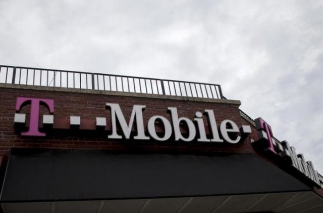People pass by a T Mobile store in the Brooklyn borough of New York