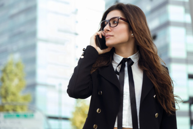 Portrait of beautiful young businesswoman using mobile phone in the street.