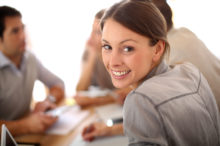 Portrait of smiling working girl in meeting