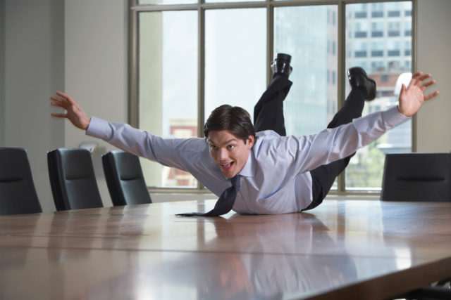 Playful Businessman Laying on Table