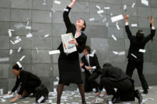 Business people on street catching falling money