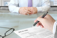 Interviewers hand with pen poised above resume