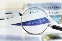 Wages Headline through magnifying glass.