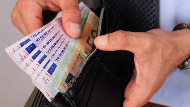 Man taking money out of wallet full of euro banknotes.
