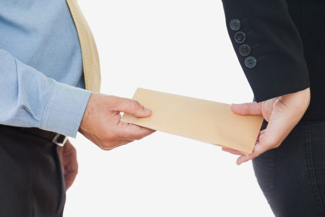 Businessman exchanging bribe with female coworker