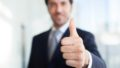 A blurry image of a businessman giving a clear thumbs up