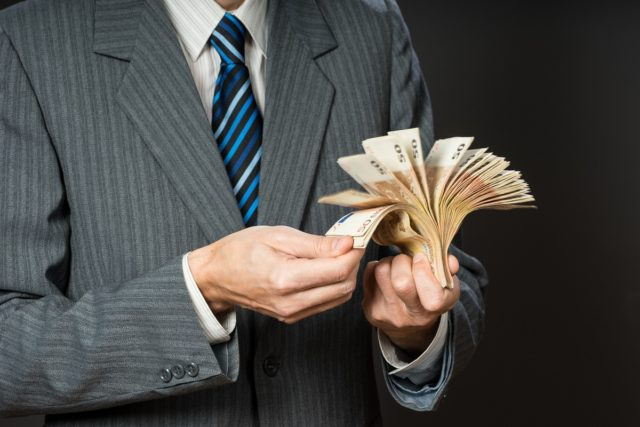 Businessman hand holding money, euro bills, stack of fifty euros