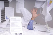 Business man drowning in paperwork