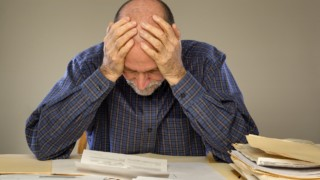 Depressed Senior Adult Man With Stacks of Papers and Envelopes