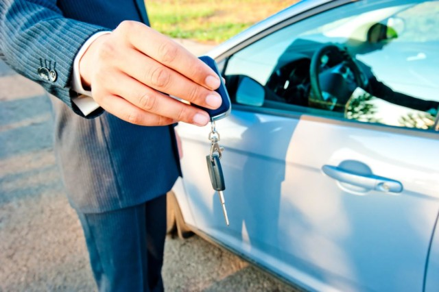 Man manager transmits the key to the new car buyer