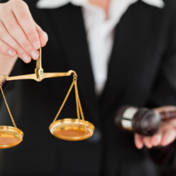 Young woman holding scales of justice and a gavel with the camera focus on the scales