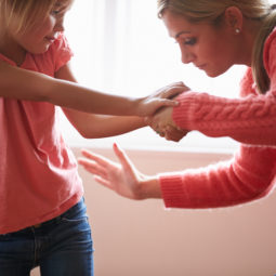 Mother in pink smacking young daughter
