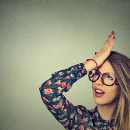 Silly woman slapping hand on head having duh moment