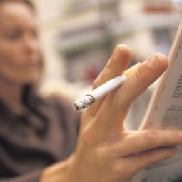 Woman Smoking and Reading the Paper