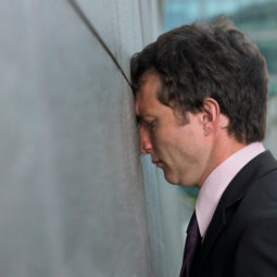 Businessman with face pressed against wall, profile, close up