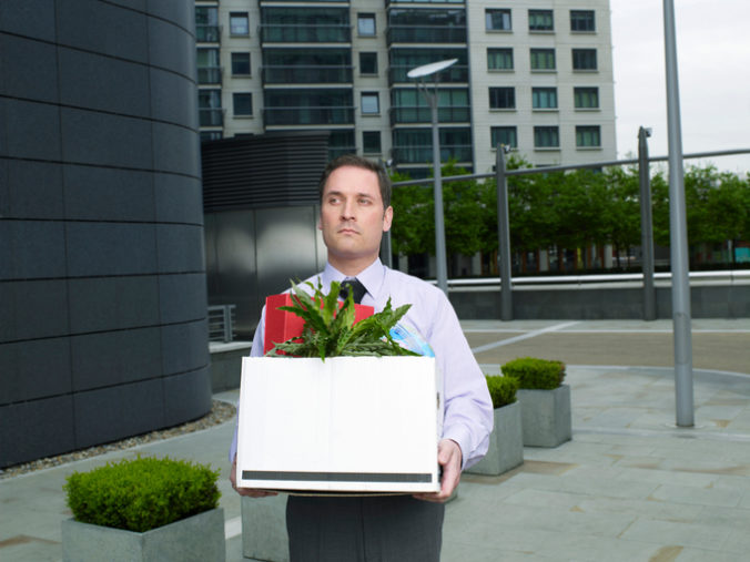Businessman carrying box containing plant and files on street