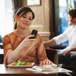 Woman sitting at table in bar, looking at mobile phone, smiling