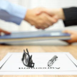 Businessman and businesswoman are shaking hands and exchanging folder