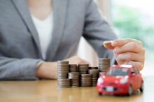 Businesswoman a toy car and a stack of coins