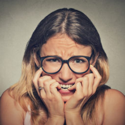Stressed anxious woman in glasses biting fingernails