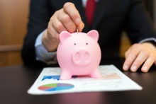 Piggy bank and business documents on desk