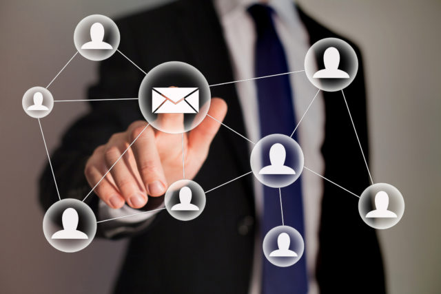 Email and contact symbols in front of businessman
