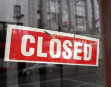 Red and white closed sign hanging in a shop window