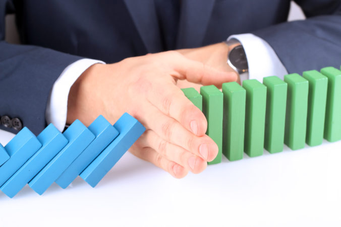 Close up of businessman stopping the effect of domino with hand