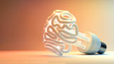 An illuminated fluorescent light bulb in the shape of a stylized brain on an isolated colorful studio background