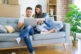 Young couple moving to a new home relaxing sitting on the sofa u