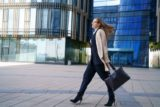Business woman in a coat and suit goes near the business