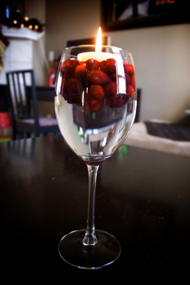 Floating candle in wine glass with water and cranberries.jpg